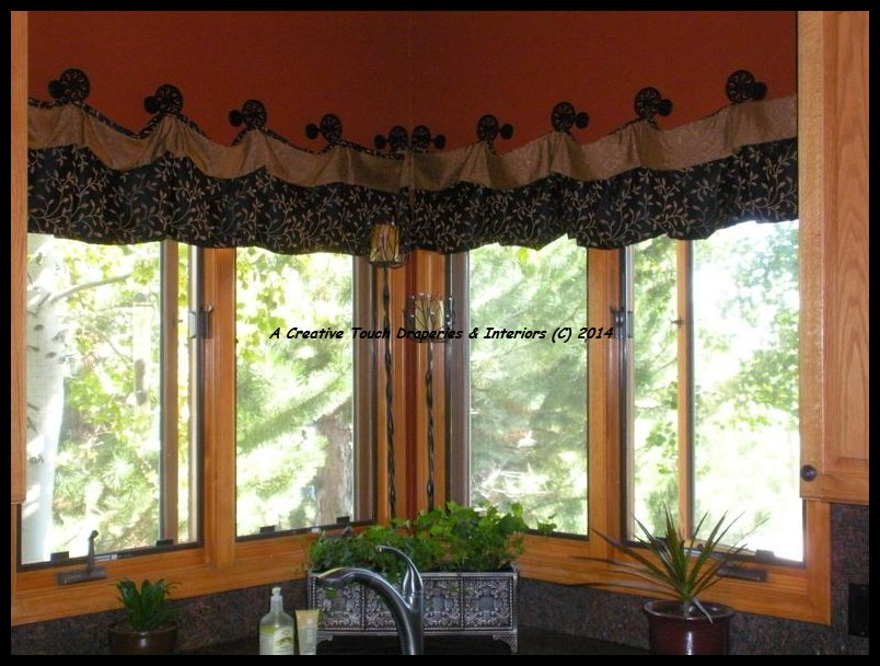 Valance hanging from knobs in corner windows